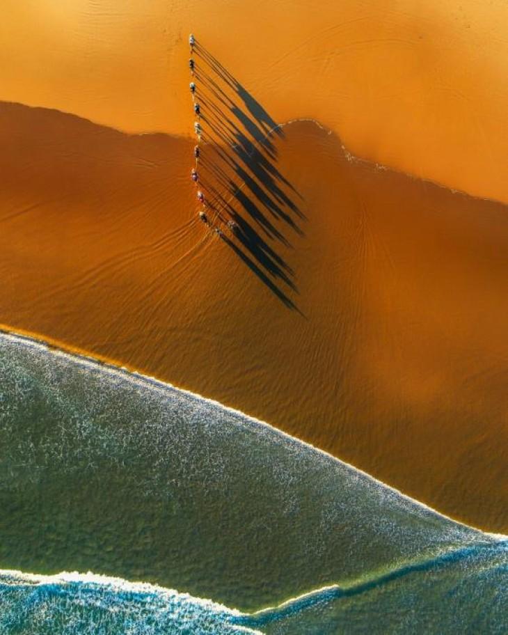Cămilele creează umbre lungi în timp ce transportă oameni de-a lungul plajei Stockton, New South Wales, Australia JIM PICYT